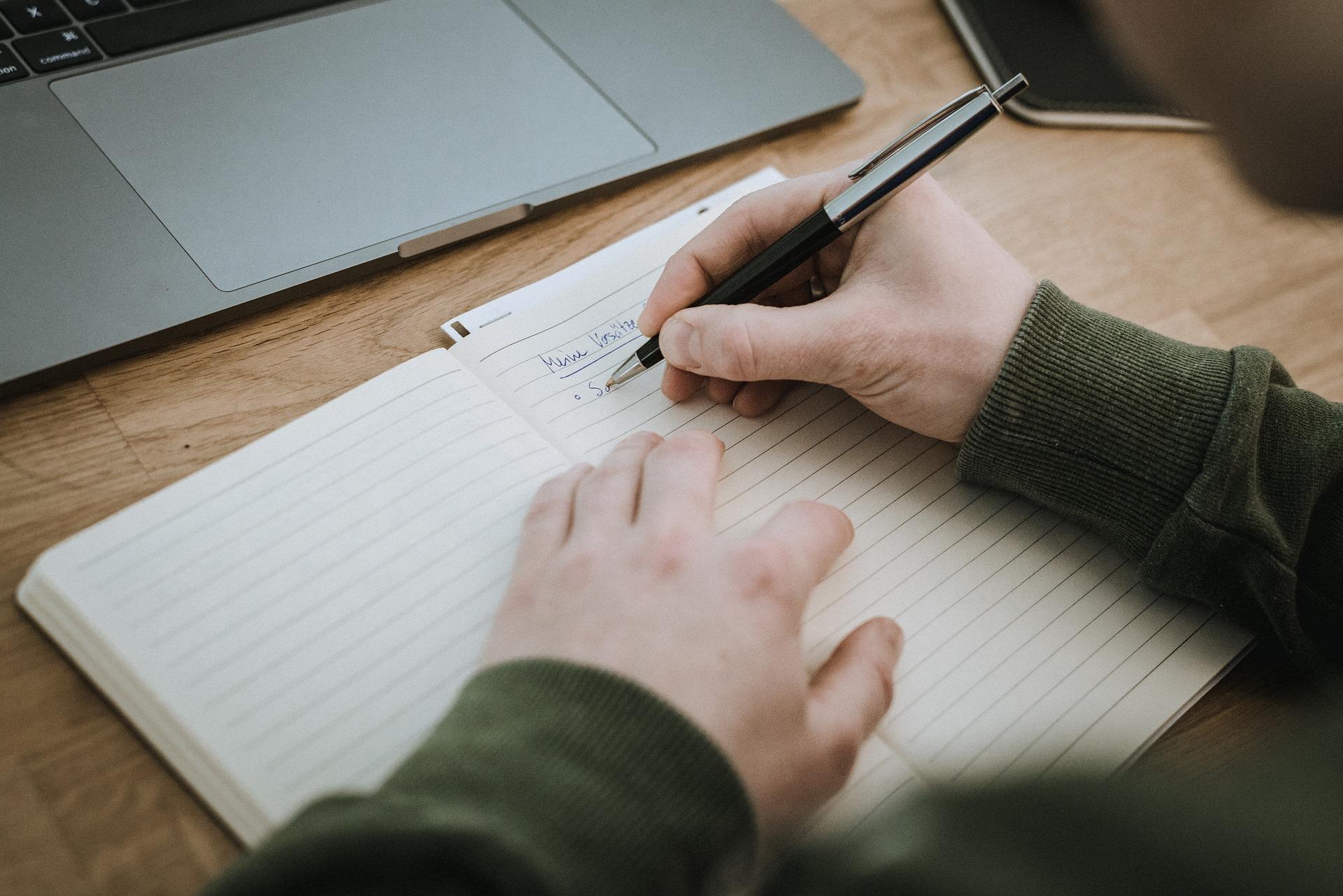 Un estudiante escribe algo en una libreta