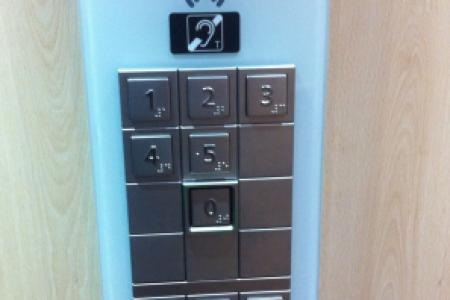 Botonera de ascensor con símbolo de bucle magnético